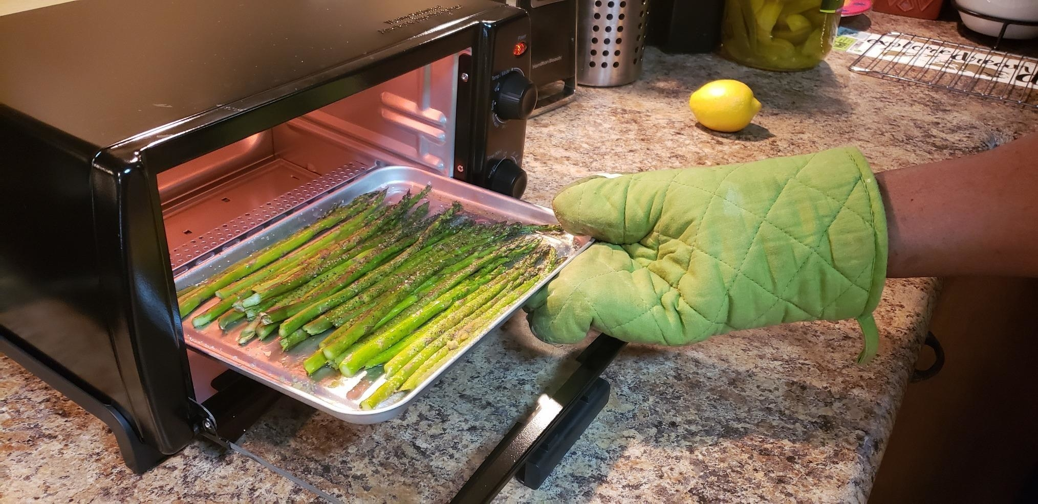 Reviewer photo of asparagus being taken out of the toaster oven