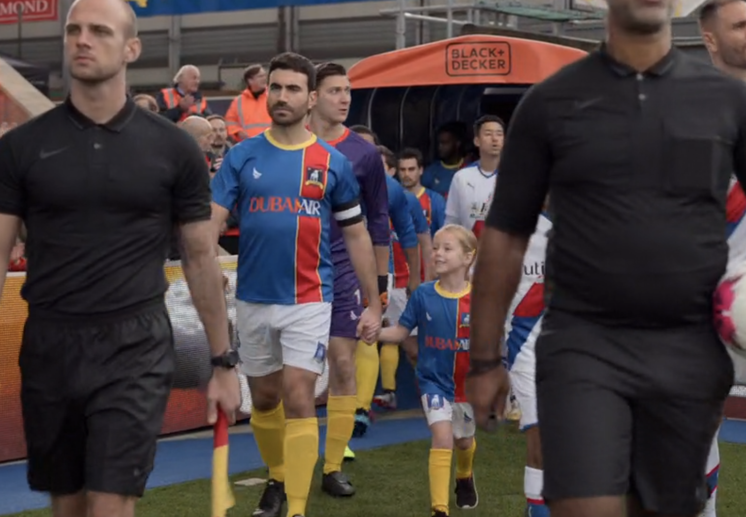 Roy and the rest of the team walk onto the field. Roy is hand in hand with his niece, Phoebe.