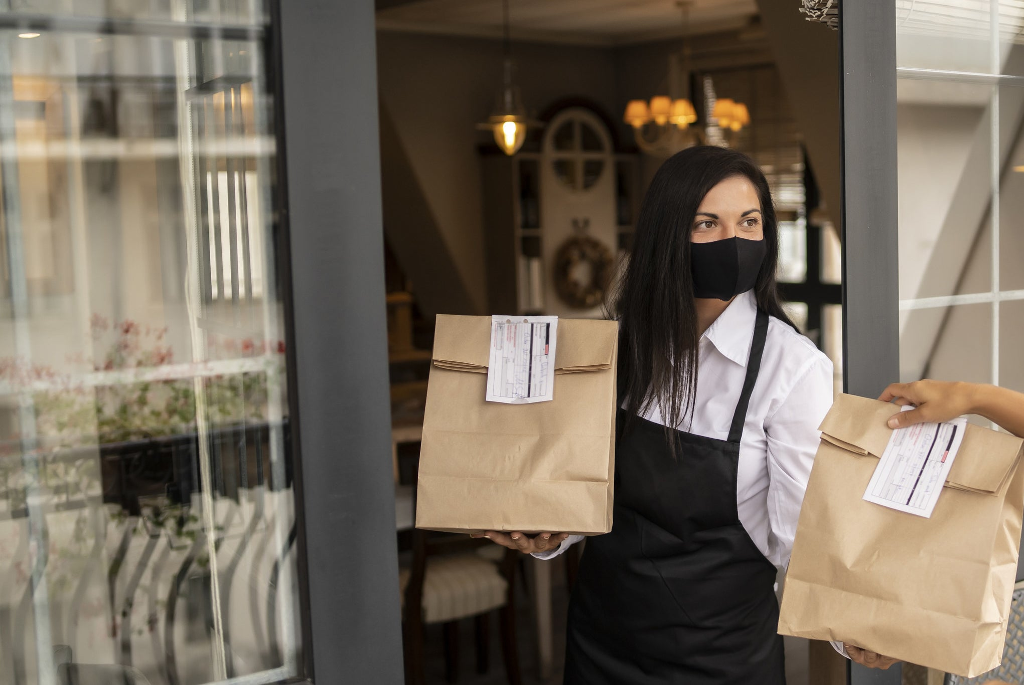 A server handing off a to-go order at a restaurant