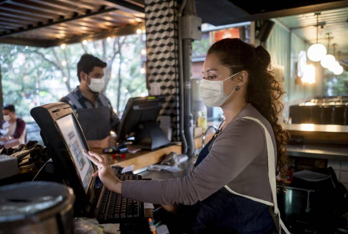 A masked server at a restaurant enters a customer's order into the POS system