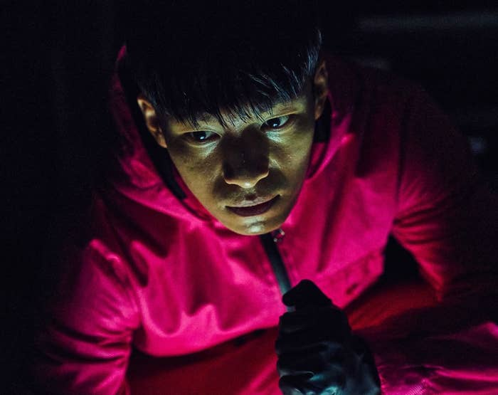 Jun-ho kneels down with a torch in a dark area