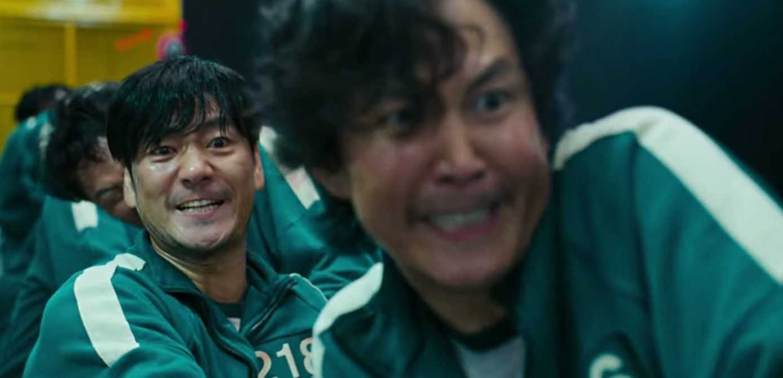 Gi-hun and Sang-woo look pained as they play tug of war