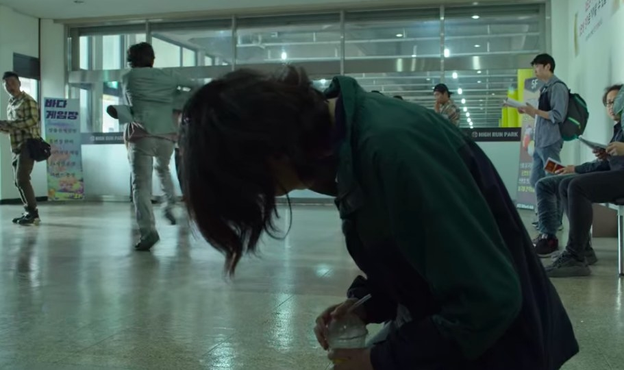 Gi-hun runs away as Sae-byeok kneels on the ground holding a cup of iced coffee