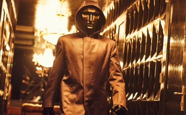 The masked Front Man walks down a corridor