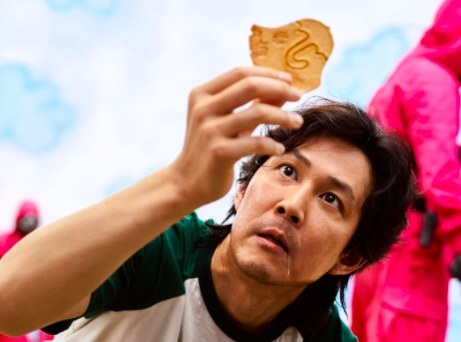 Gi-hun holds up his piece of dalgona and looks at it
