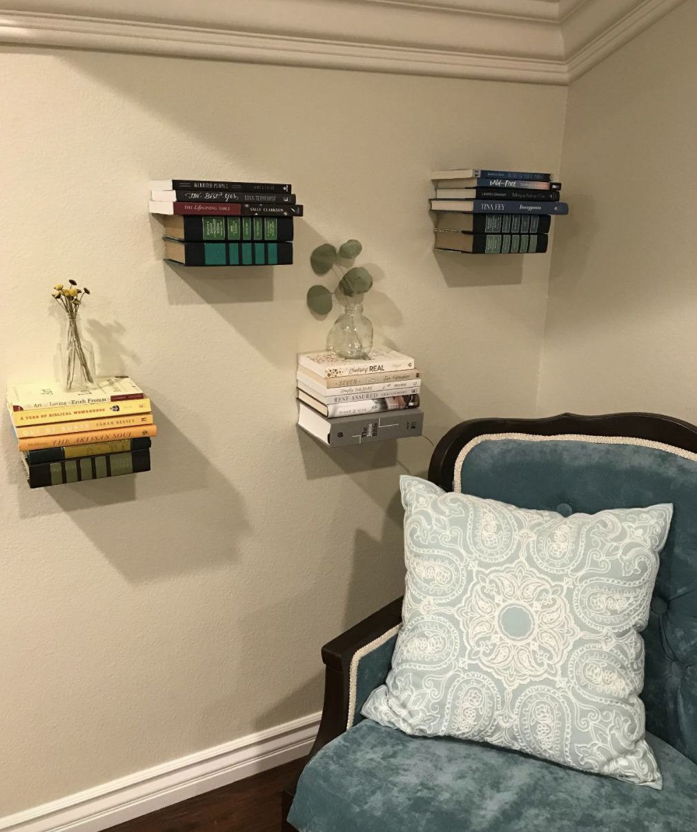 A customer review photo of their floating bookshelves on a wall next to a chair