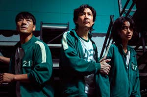 Sang-woo, Gi-hun, and Sae-byeok stand in a row in front of beds in the dormitory
