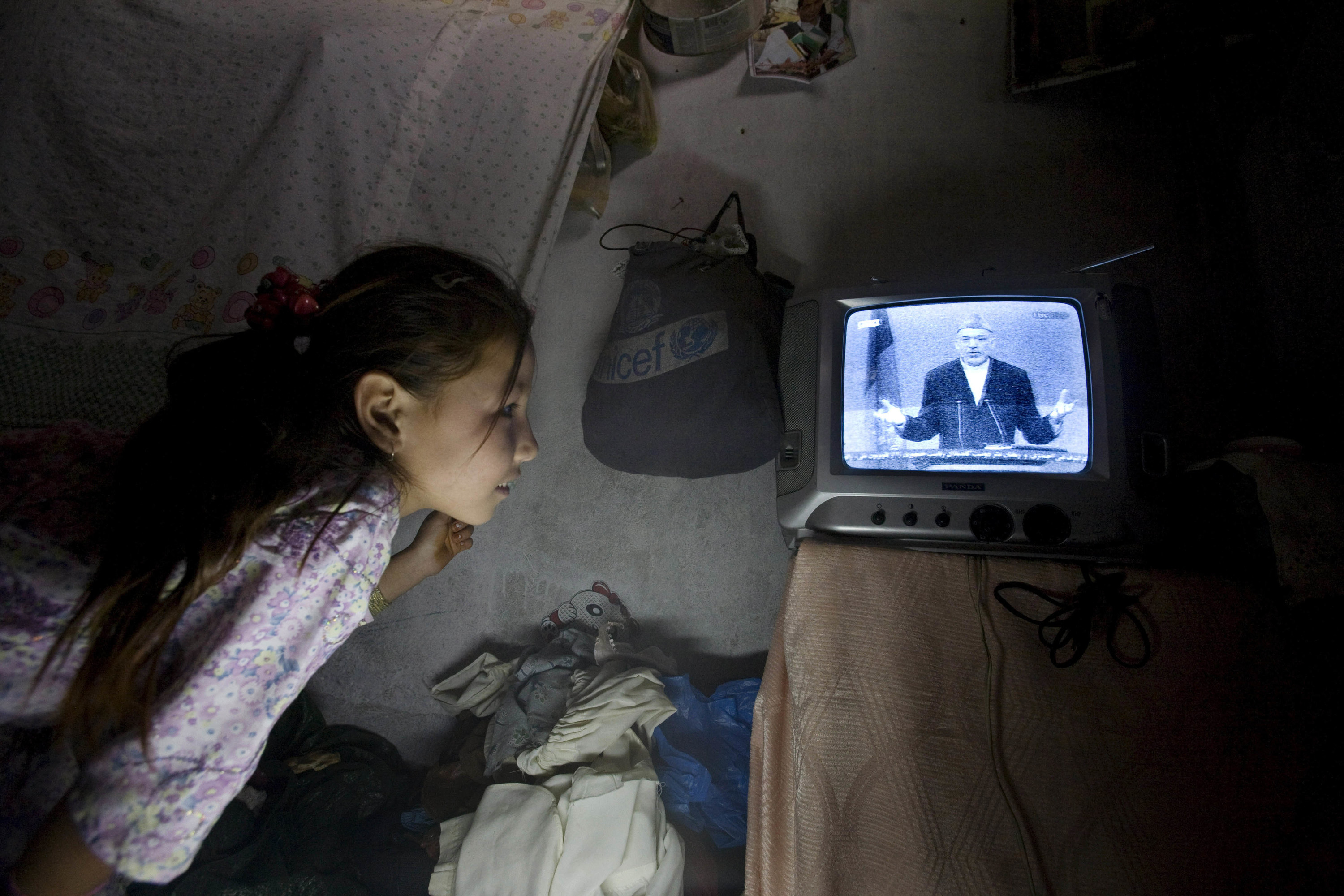 A girl gazes at a small TV and watches then–Afghan president Hamid Karzai speaking at a podium during the presidential candidates' live debate in Kabul, Afghanistan, in 2009