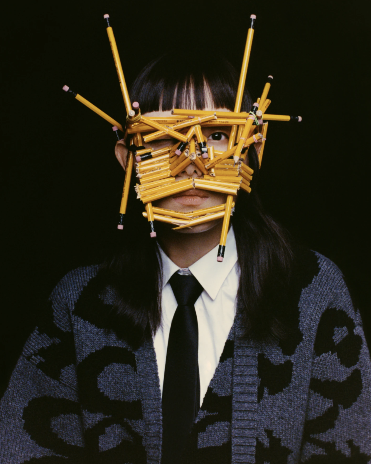 A person in a sweater looks at the camera, with their face covered by numerous pencils bundled together in several directions