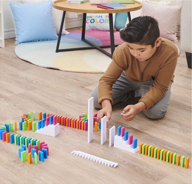 Persona jugando con las fichas de dominó de colores neón