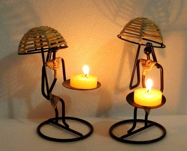 Two women-shaped candle holders holding a candle