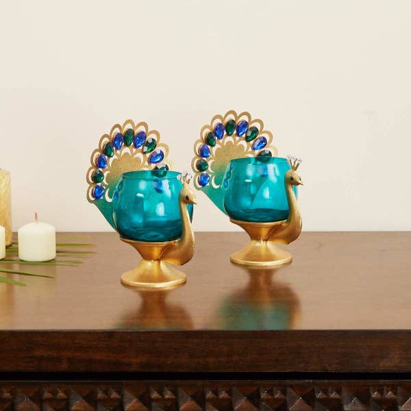Two peacock tealight holders on a table
