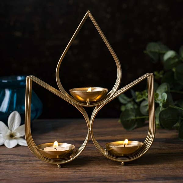 Three tealights balanced in teardrop shaped metal