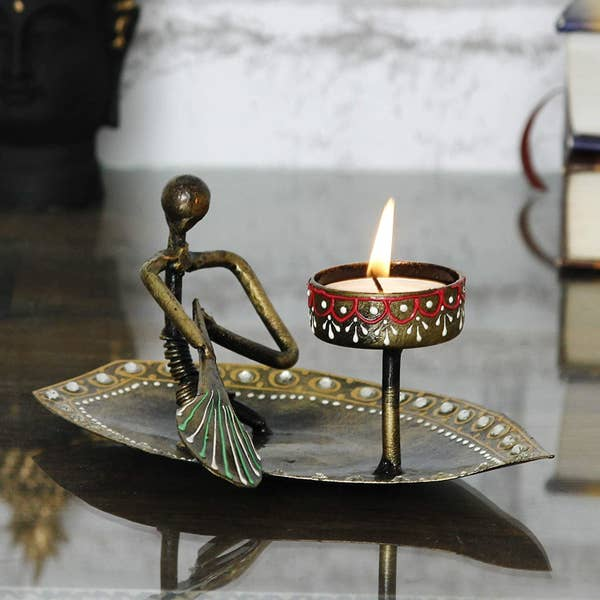 A boat-shaped candle holder with a figurine rowing