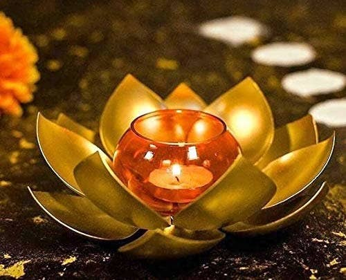 A lotus shaped candle holder with a lit candle in the middle
