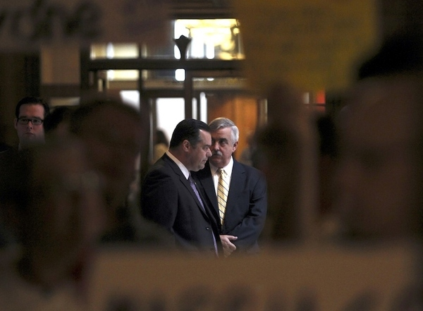 Lobbyists are seen between protesters signs at the Capitol in Albany, N.Y., on Friday, June 24, 2...