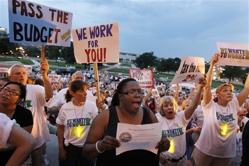 Hundreds of demonstrators, including state worker Michelle Lewis, center, of Hastings, Minn., hol...