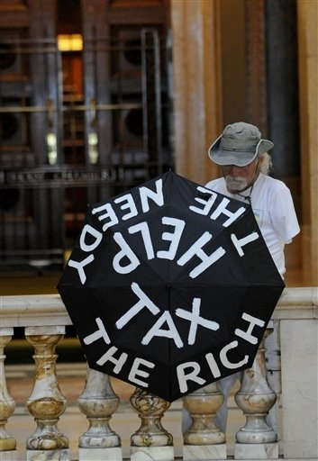 A demonstrator stood on the Minnesota Capitol rotunda balcony outside the House of Representative...