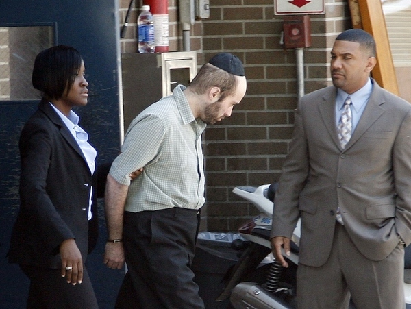 Detectives walk Levi Aron, center, to a police car at the Brooklyn borough of New York's 67th...