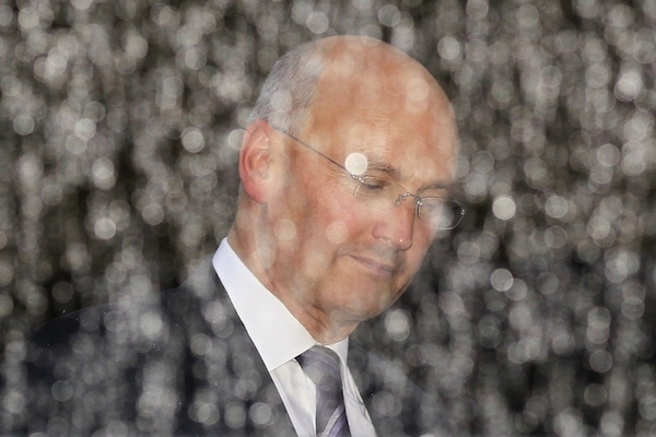 Photographed through a glass wall in the rain, Metropolitan Police commissioner Sir Paul Stephens...