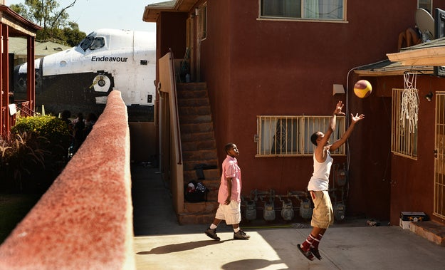 """""""Traymond Harris (L) and Ryan Hudge play basketball as Space Shuttle Endeavour travels to the California Science Center on Crenshaw Ave in Inglewood, Los Angeles on Saturday.The shuttle was moving at 2mph, so no high speed lens needed."""