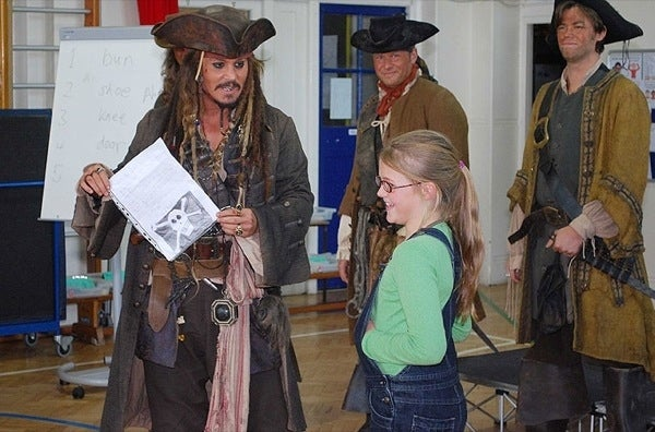 "Johnny Depp paid a surprise visit to a London school dressed as pirate, Jack Sparrow. The visit came after nine-year-old student Beatrice Delap asked for the Captain's help in staging a mutiny against her teachers. Before leaving, Depp reminded the students to stay in school, ""as pirates have to be cleverer than everyone else""."