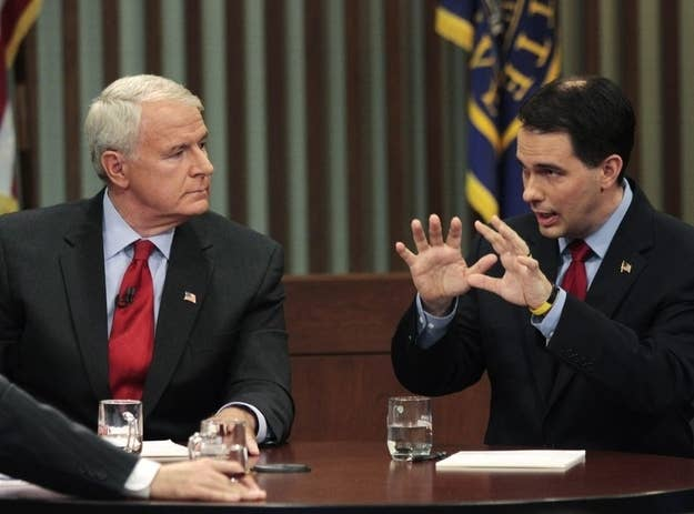 Milwaukee Mayor Tom Barrett (L) and Republican Wisconsin Governor Scott Walker talk during a debate held at Marquette University Law School yesterday.