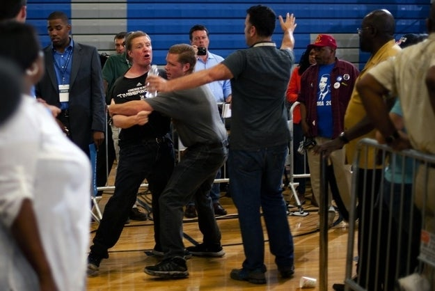 A protester (C) is held back by two supporters as he shouts while US President Barack Obama delivers remarks during a campaign event at Canyon Springs High School in Las Vegas, Nevada, August 22, 2012.