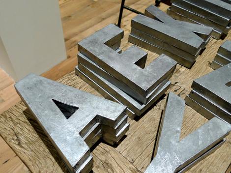 Spraypaint papier-mâché letters to create zinc alphabet letters.