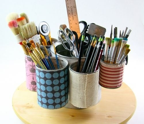 Cover tin cans with Mod Podge and fabric, then use wire to attach them around the perimeter of a larger can. Nifty storage for paint brushes, pencils, and other art supplies.