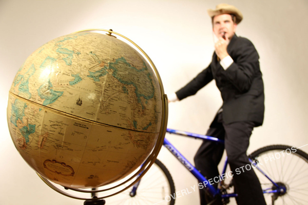 Pipe-Smoking Australian Businessman Riding Bike with Globe in Foreground