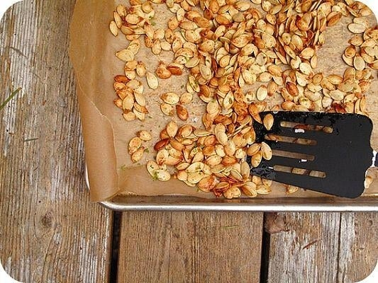 Preheat the oven to 375 degrees F. Scatter pumpkin seeds in a single layer on a baking sheet. Drizzle with olive oil, sprinkle with salt, mix together. Bake for about 7 minutes, until light brown and crispy.