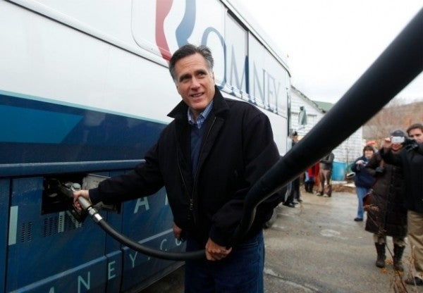 Mitt Romney pumps gas in his campaign bus.