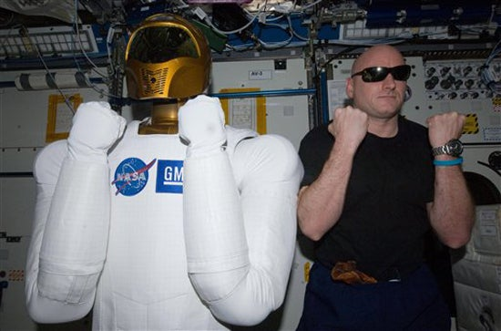 In this March 15, 2011 file photo provided by NASA, astronaut Scott Kelly, Expedition 26 commander, right, poses with Robonaut 2, the dexterous humanoid astronaut helper, in the Destiny laboratory of the International Space Station. NASA ground controllers on Monday, Aug. 22, 2011 turned on the robot for the first time since it was delivered to the International Space Station in February.