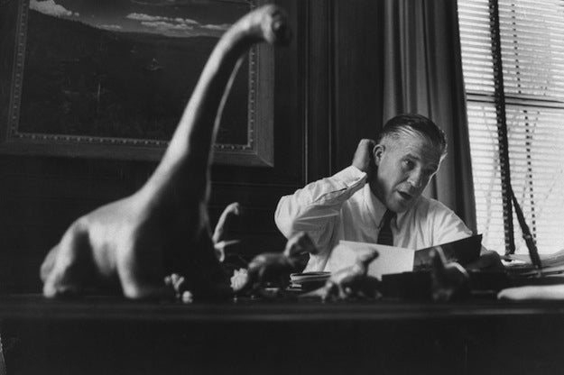 """A caption from the March 1958 issue of LIFE: """"On desk George Romney keeps prehistoric animals to remind him of favorite 'big-car' analogy. 'Some dinosaurs had a 70-foot wheelbase and huge fuel consumption. The principal factor in their extinction was the fact that they got so big they were unable to live.'"""""""