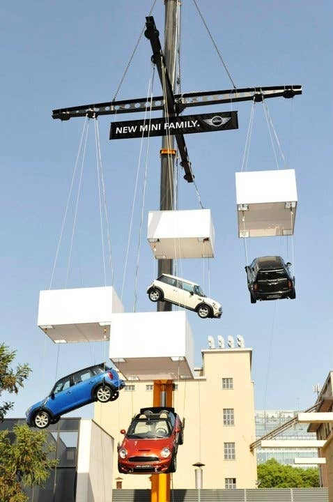 A giant mobile comprised of four full-sized MINI cars hang suspended in the air in Milan.