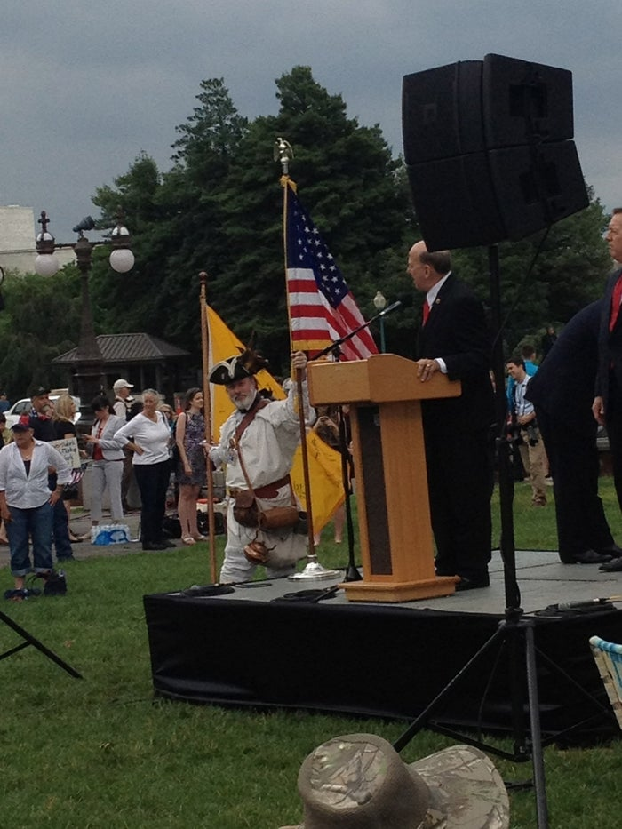 Rep. Louie Gohmert speaks to the crowd. An attendee holds up the American flag.