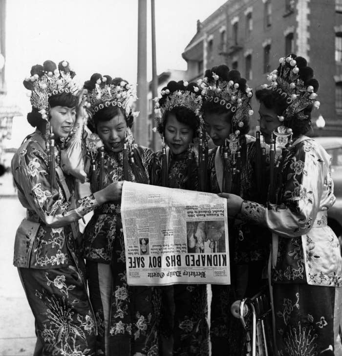 Five women dressed in traditional Chinese clothing read the day's headlines.