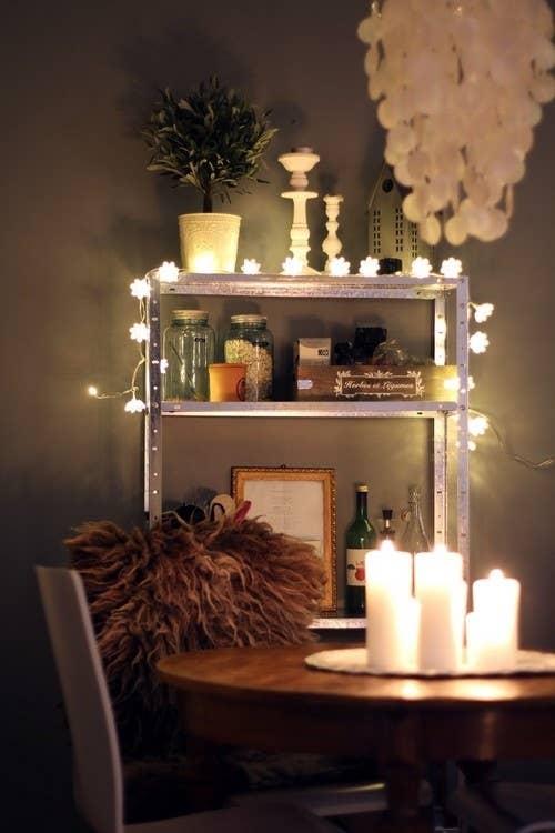 Drape lights over a bookshelf. 46 Awesome String Light DIYs For Any Occasion