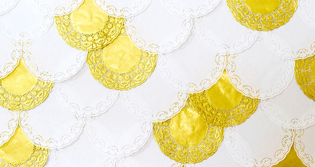 Layer different colored doilies on a wall.