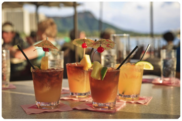 """No Luau is complete without the iconic Mai Tai made of fresh tropical juices, dark rum, dressed up with a pineapple wedge and an umbrella! Vic originally created the Mai Tai as a showcase for a 17 year aged rum, with nary a fruit juice in the mix. """"The flavor of this great rum wasn't meant to be overpowered with heavy additions of fruit juices and flavorings,"""" mused Vic, however, his stern statement has since evaporated into the ether much like that of the concept of the original martini. The """"proper"""" Mai Tai recipe has a deep amber hue, resulting from the rums used to concoct the libation and not from any fruit juices or colored sweeteners. Trader Vic's original aged rum is no longer available, but today's rums make for perfect rum drinks, including the ubiquitous Trader Vic's Mai Tai. Get Recipe"""