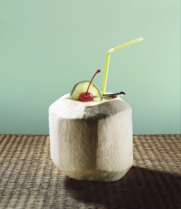 Drink something out of a coconut.