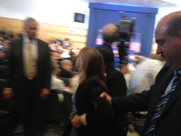 Medea Benjamin being led out of the auditorium during Obama's speech.