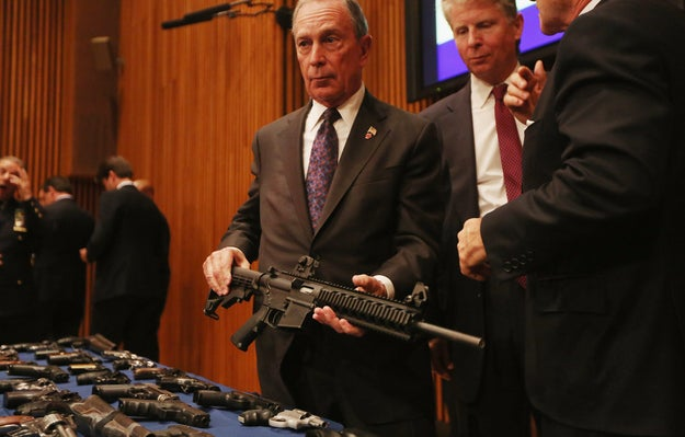Bloomberg displays a confiscated AR-15 assault rifle above a table of illegal firearms sold to undercover officers.