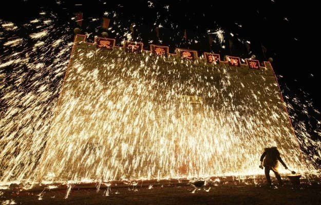 A traditional performer sprays molten iron against a concrete wall to celebrate the Lantern Festival in China.