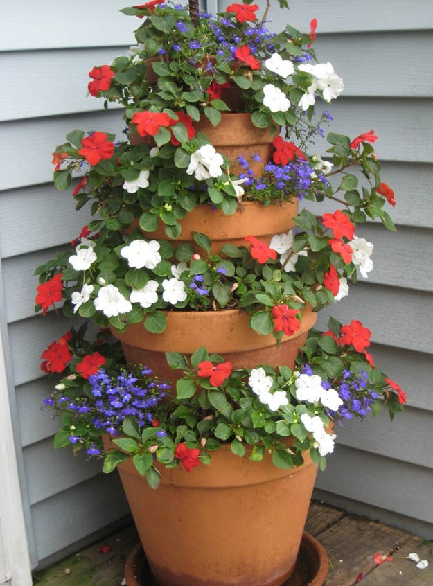 If you only have a small corner of space, then stack terracotta planters for overflowing flowers. DIY here .