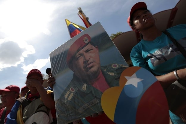A supporter of the late Venezuelan President Hugo Chavez holds a portrait of Chavez while waiting at the street as his coffin is driven through the streets of Caracas, March 6, 2013.