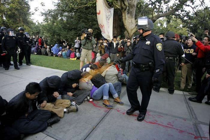 A University of California Davis police officer pepper-sprays students during their sit-in on November 18, 2011.