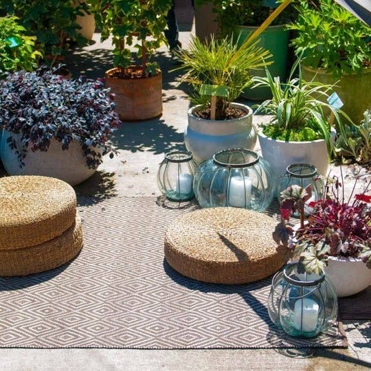 Create A Backyard Hangout Spot With Pillows Rug Lights And Plants
