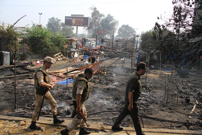 Members of the Egyptians Army walk among the smoldering remains of the largest protest camp of supporters of ousted President Mohammed Morsi, that was cleared by security forces, in Cairo.